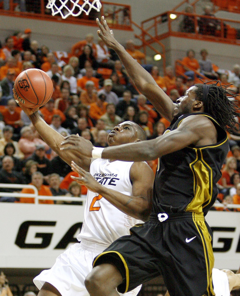 OSU's Obi Muonelo goes past Missouri's DeMarre Carroll during the Big 12 college basketball game between Oklahoma State and Missouri at Gallagher-Iba Arena in Stillwater, Okla., Wednesday, Jan. 21, 2009.  PHOTO BY BRYAN TERRY, THE OKLAHOMAN