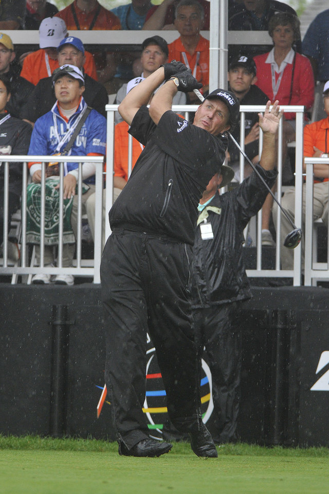 Photo - Phil Mickelson tees off on the first hole of the final round of the Bridgestone Invitational golf tournament, Sunday, Aug. 3, 2014, in Akron, Ohio. (AP Photo/Phil Long)