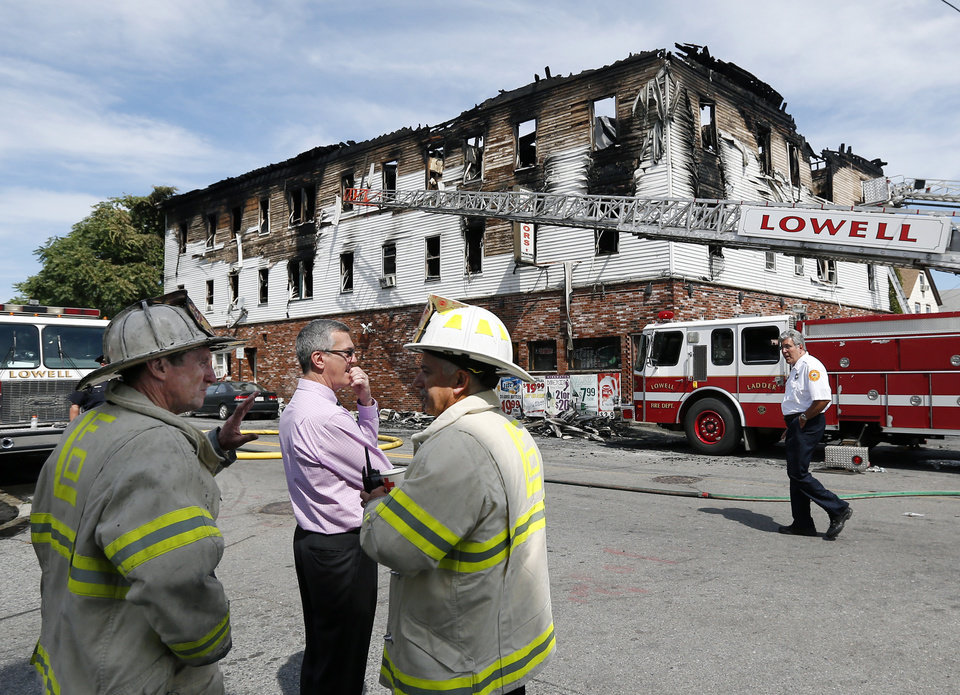 Photo - Fire officials observe the scene of a burned three-story apartment and business building in Lowell, Mass., Thursday, July 10, 2014, where officials said seven people died in a fast-moving pre-dawn fire. All seven victims were found in third-floor units of the three-story building that had businesses on the ground floor and apartments on the upper floors, fire officials said.  (AP Photo/Elise Amendola)