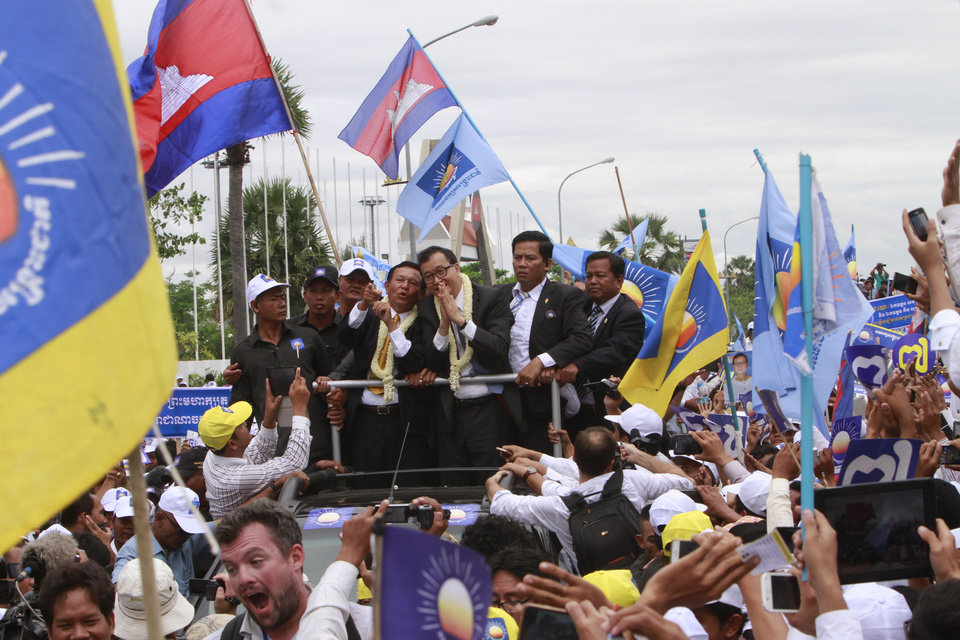 Photo - Sam Rainsy, center right, president of Cambodia National Rescue Party (CNRP) greets together with his party's Vice President Kem Sokha, center left, to supporters on the main street in Phnom Penh, Cambodia, Friday, July 19, 2013. Thousands of cheering supporters greeted Cambodian opposition leader Rainsy as he returned from self-imposed exile Friday to spearhead his party's election campaign against well-entrenched Prime Minister Hun Sen. (AP Photo/Heng Sinith)