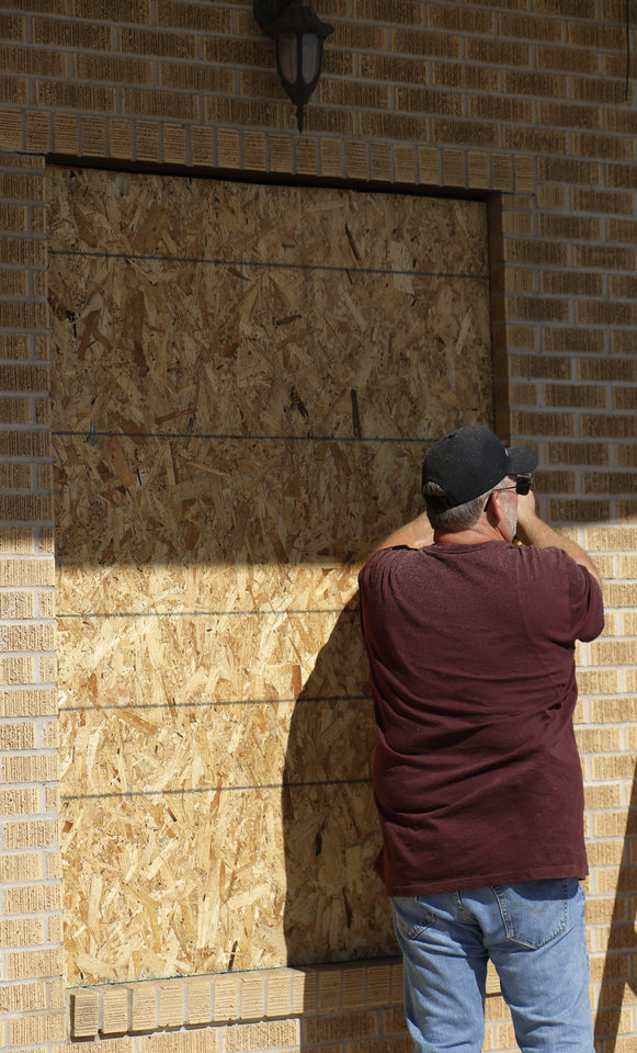 Photo - A man boards up a broken window at CJ's Bail Bonds on Classen Blvd. Damage from Saturday night protest in downtown Oklahoma City, Sunday, May 31, 2020. [Doug Hoke/The Oklahoman]