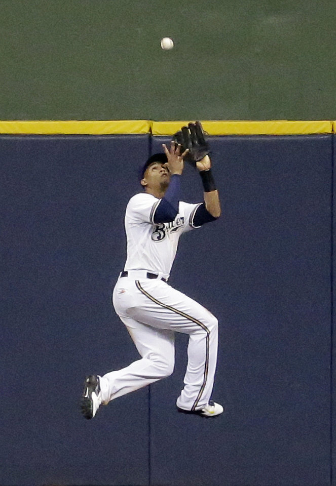 Photo - Milwaukee Brewers center fielder Carlos Gomez leaps and catches a ball hit by Minnesota Twins' Trevor Plouffe during the eighth inning of a baseball game, Monday, June 2, 2014, in Milwaukee. (AP Photo/Morry Gash)