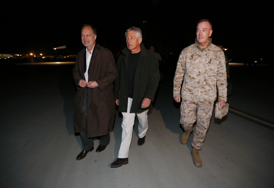 Photo - U.S. Secretary of Defense Chuck Hagel walks with U.S. Ambassador to Afghanistan James Cunningham, left,  and General Joseph Dunford, Commander of the International Security Force, upon Hagel's arrival in Kabul, Afghanistan, Friday, March 8, 2013.  (AP Photo/Jason Reed, Pool)