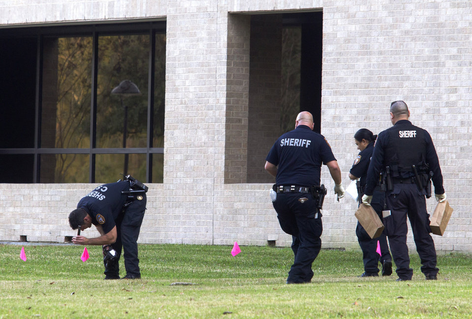Photo - Police collect evidence after a shooting happened on Lone Star College North Harris campus on Tuesday January 22, in Houston. The shooting at a community college wounded three people Tuesday and sent some students fleeing for safety while others with medical training helped tend the wounded.   (AP Photo/ Patric Schneider)