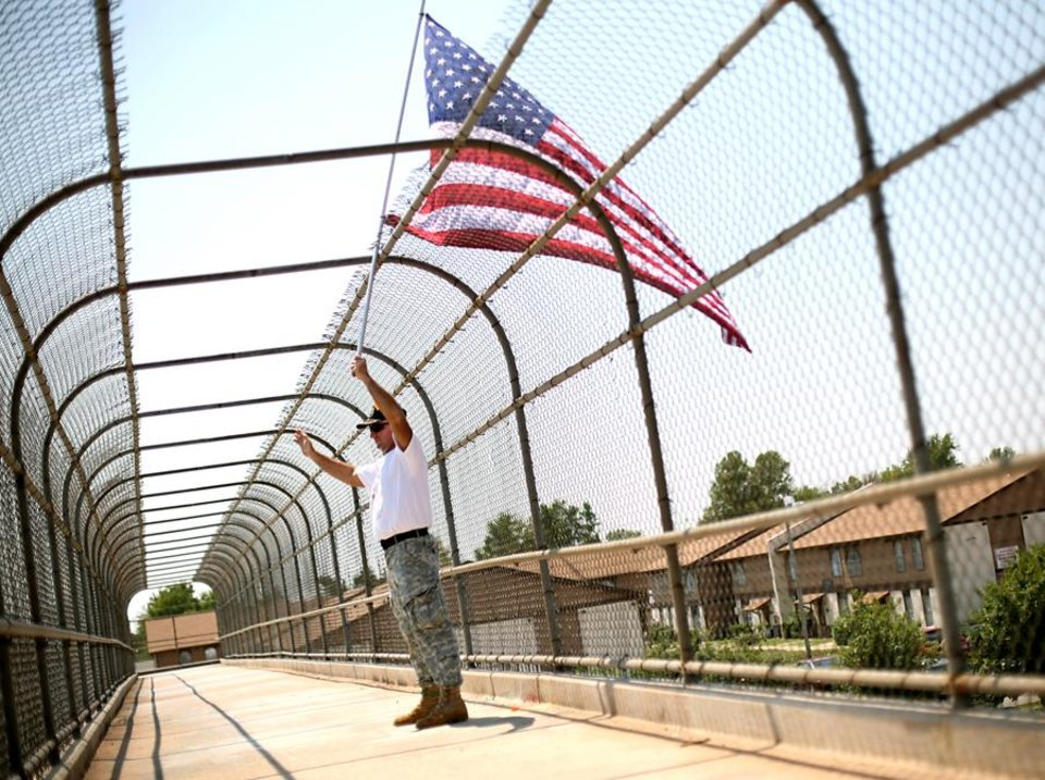 Photo -  Standing on a pedestrian bridge, Ted Krey, of Yukon, holds an American Flag over I-240 on Wednesday, Aug. 24, 2011. Krey says he will hold the flag over traffic from a different pedestrian bridge around Oklahoma City everyday until Sept. 11. Photo by John Clanton, The Oklahoman
