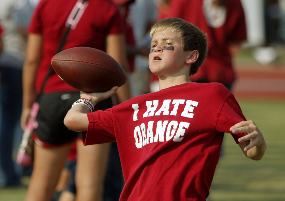 Photo - Alex Williams, 12, of Norman throws a football before the college football game between the University of Oklahoma Sooners (OU) and the Tulsa University Hurricanes (TU) at the Gaylord Family-Memorial Stadium on Saturday, Sept. 3, 2011, in Norman, Okla. 