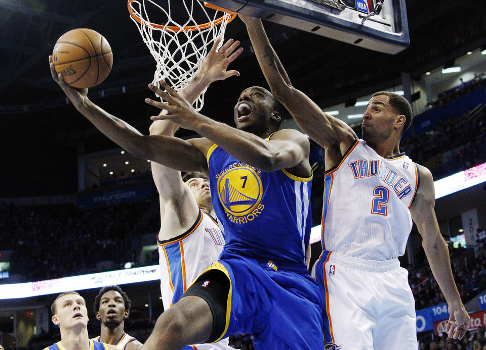 Golden State Warriors forward Carl Landry (7) shoots between Oklahoma City Thunder forward Nick Collison, left, and guard Thabo Sefolosha (2) in the first quarter of an NBA basketball game in Oklahoma City, Sunday, Nov. 18, 2012. (AP Photo/Sue Ogrocki)