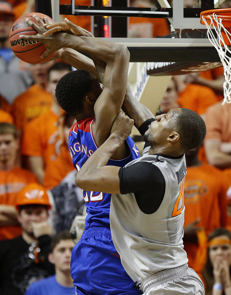 Photo - Oklahoma State's Kamari Murphy (21) fouls Kansas' Andrew Wiggins (22) during an NCAA college basketball game between Oklahoma State University (OSU) and the University of Kansas at Gallagher-Iba Arena in Stillwater, Okla., Saturday, March 1, 2014. Oklahoma State won 72-65. Photo by Bryan Terry, The Oklahoman