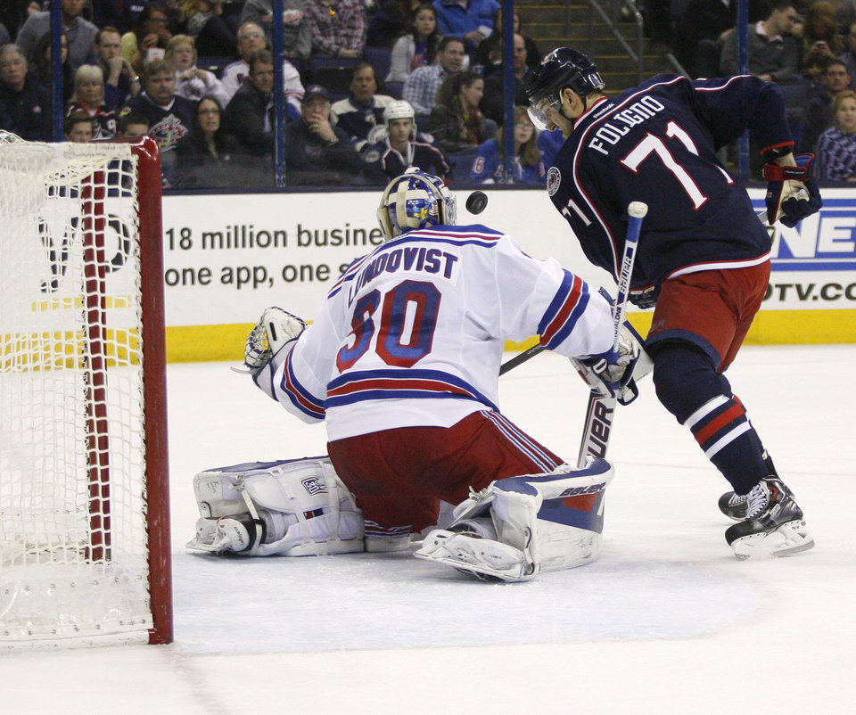 Photo - Columbus Blue Jackets' Nick Foligno (71) shoots against New York Rangers goalie Henrik Lundqvist (30), of Sweden, during the second period of an NHL hockey game, Friday, March 21, 2014, in Columbus, Ohio. (AP Photo/Mike Munden)