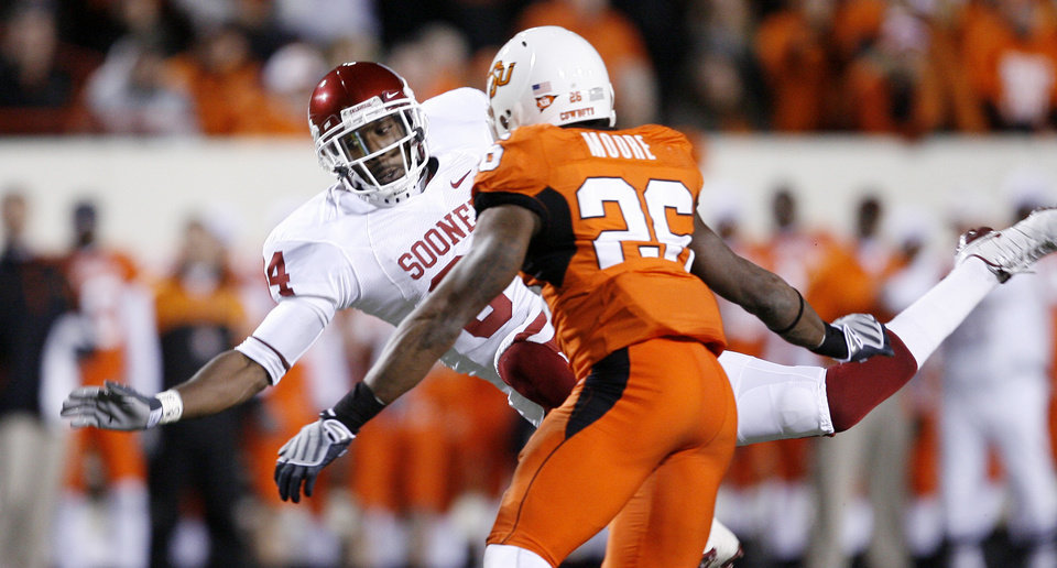Sooner Quentin Chaney falls as Quinton Moore of OSU closes in during the first half of the college football game between the University of Oklahoma Sooners (OU) and Oklahoma State University Cowboys (OSU) at Boone Pickens Stadium on Saturday, Nov. 29, 2008, in Stillwater, Okla. STAFF PHOTO BY BRYAN TERRY