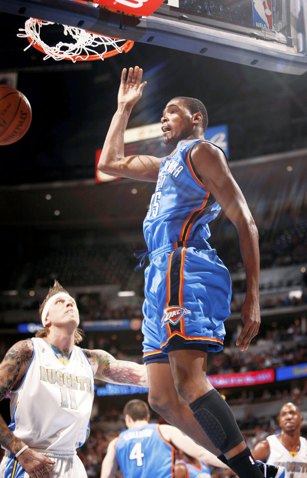 Photo - Thunder forward Kevin Durant, front, hangs in the air after dunking the ball over Denver's Chris Andersen during Oklahoma City's 102-93 loss Monday in Denver.  AP PHOTO