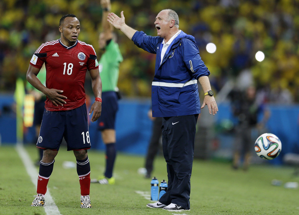 Photo - Colombia's Juan Zuniga waits to get the ball as Brazil's coach Luiz Felipe Scolari yells instructions to his players during the World Cup quarterfinal soccer match between Brazil and Colombia at the Arena Castelao in Fortaleza, Brazil, Friday, July 4, 2014. Brazil defeated Colombia 2-1 to advance to the semifinals. (AP Photo/Natacha Pisarenko)