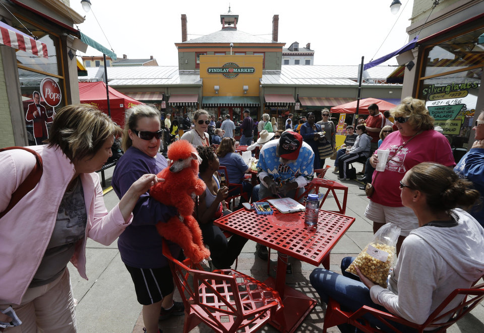 Photo - This April 14, 2013 photo shows a dyed red poodle at Findlay Market in Cincinnati. Cincinnati residents have been getting fresh meat, produce and homemade bread at Findlay Market since 1855, making it the oldest continuously running public market in the Buckeye State, (AP Photo/Al Behrman)