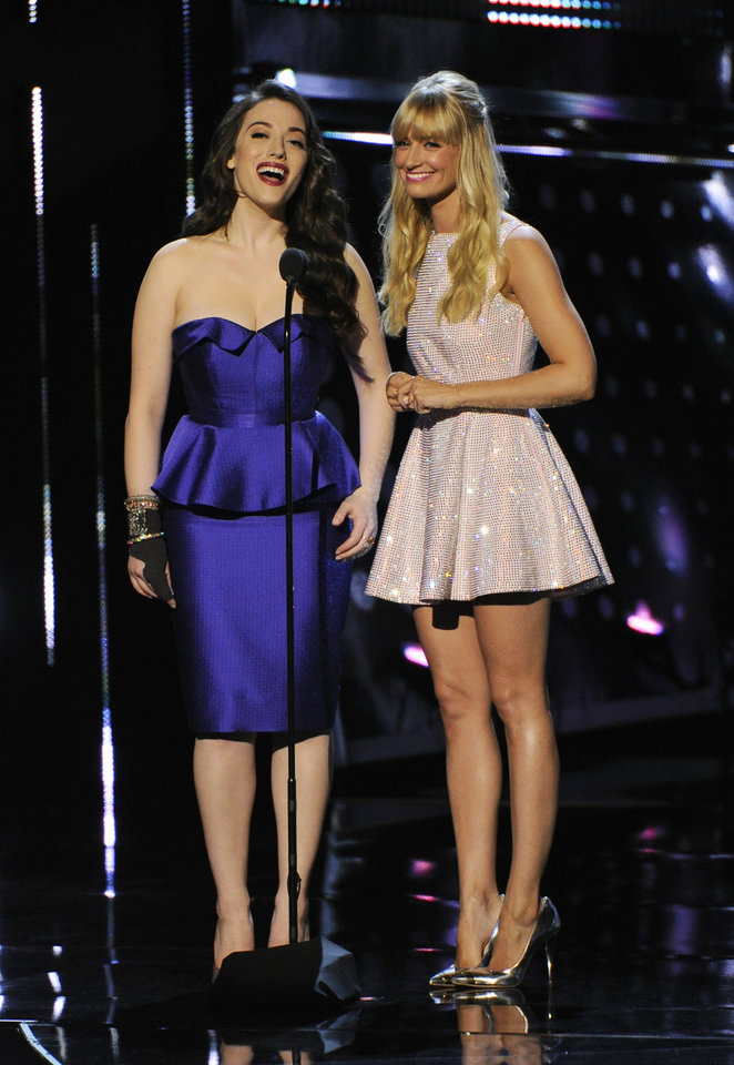 Photo - Hosts Kat Dennings, left, and Beth Behrs speak on stage at the 40th annual People's Choice Awards at the Nokia Theatre L.A. Live on Wednesday, Jan. 8, 2014, in Los Angeles. (Photo by Chris Pizzello/Invision/AP)