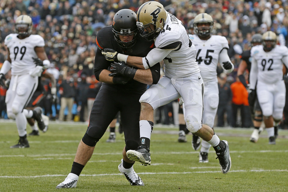 Photo - Oklahoma State's Jeremy Seaton (44) pushes past Purdue's Landon Feichter (44) to score a touchdown during the Heart of Dallas Bowl football game between Oklahoma State University and Purdue University at the Cotton Bowl in Dallas, Tuesday, Jan. 1, 2013. Oklahoma State won 58-14. Photo by Bryan Terry, The Oklahoman