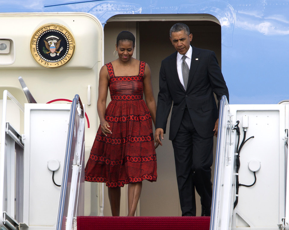 Photo - President Barack Obama and first lady Michelle Obama walk down the stairs from Air Force One upon arrival at Andrews Air Force Base, Md. on Monday, June 16, 2014. President Obama and first lady Michelle Obama are returning from Palm Springs, Calif. (AP Photo/Jose Luis Magana)