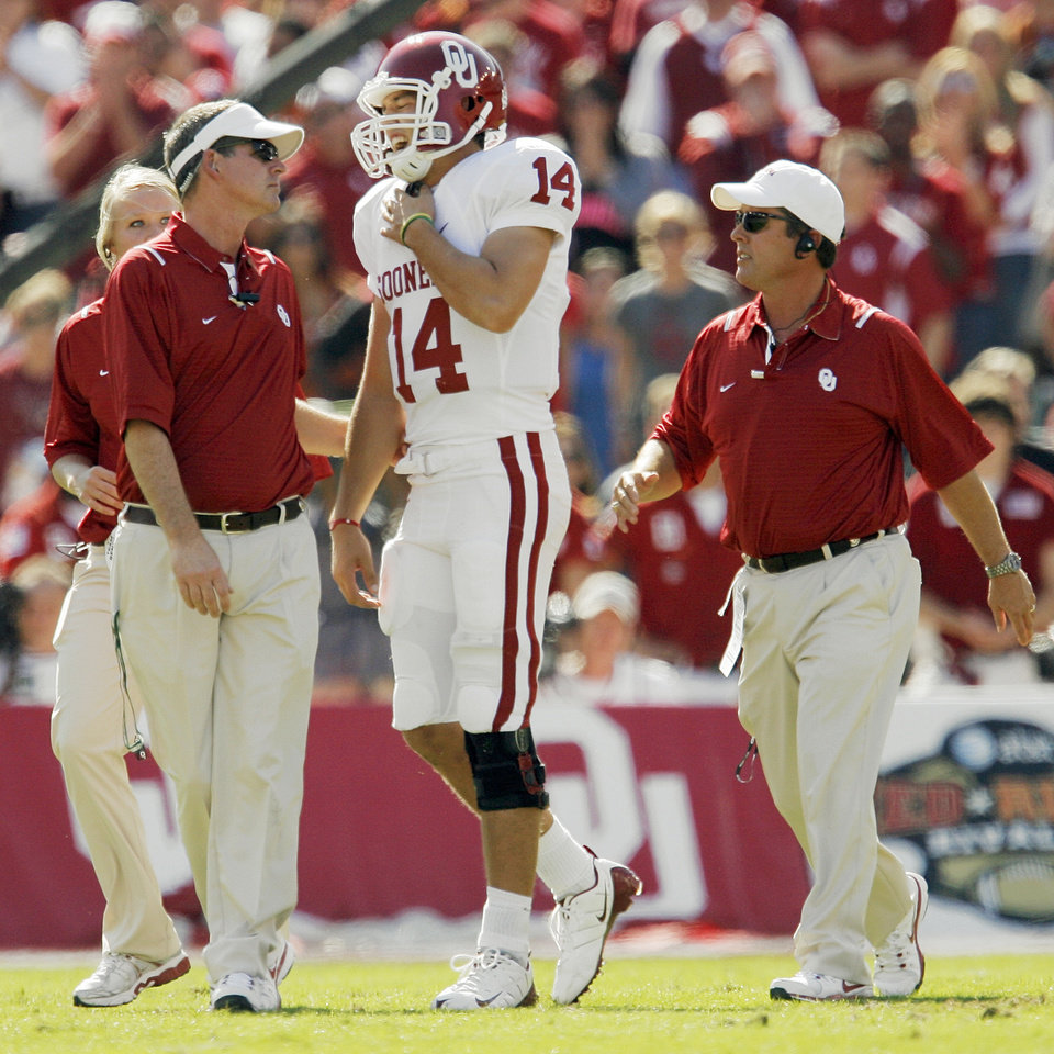 Photo - OU quarterback Sam Bradford (14) leaves the field with OU staff members after being injured in the first quarter during the Red River Rivalry college football game between the University of Oklahoma Sooners (OU) and the University of Texas Longhorns (UT) at the Cotton Bowl in Dallas, Texas, Saturday, Oct. 17, 2009. Bradford did not return to the game. Photo by Nate Billings, The Oklahoman
