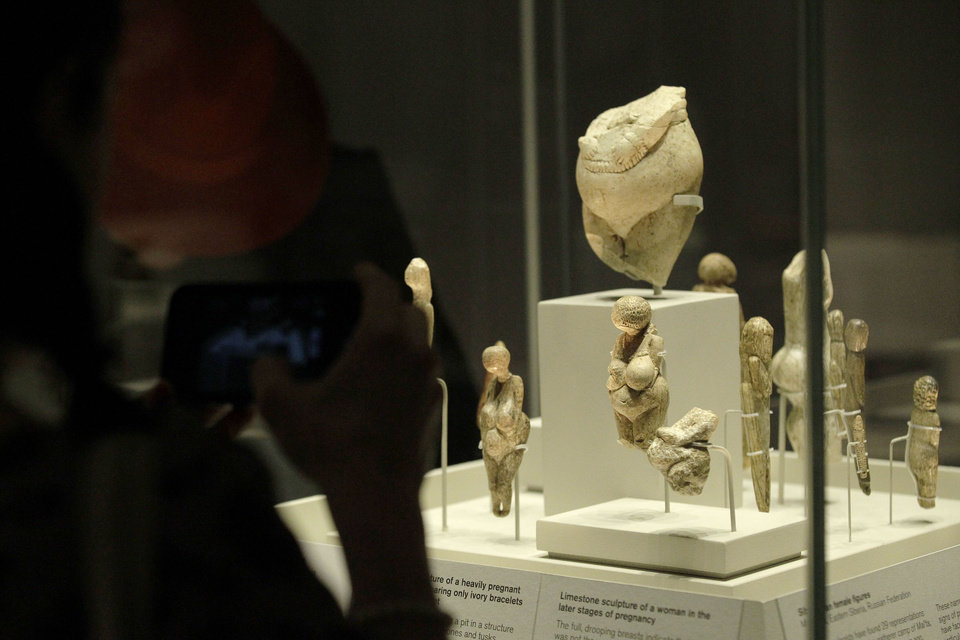 Visitors look at sculptures of pregnant women on display in an exhibition \'Ice Age Art : arrival of the modern mind\' at the British Museum in London, Tuesday, Feb. 5, 2013. The exhibition present masterpieces create from the last Ice Age between 40,000 and 10,000 years ago, drawn from across Europe, by artists with modern minds and presented alongside modern works to illustrate the fundamental human desire to communicate and make art as a way of understanding ourselves and our place in the world. (AP Photo/Sang Tan)