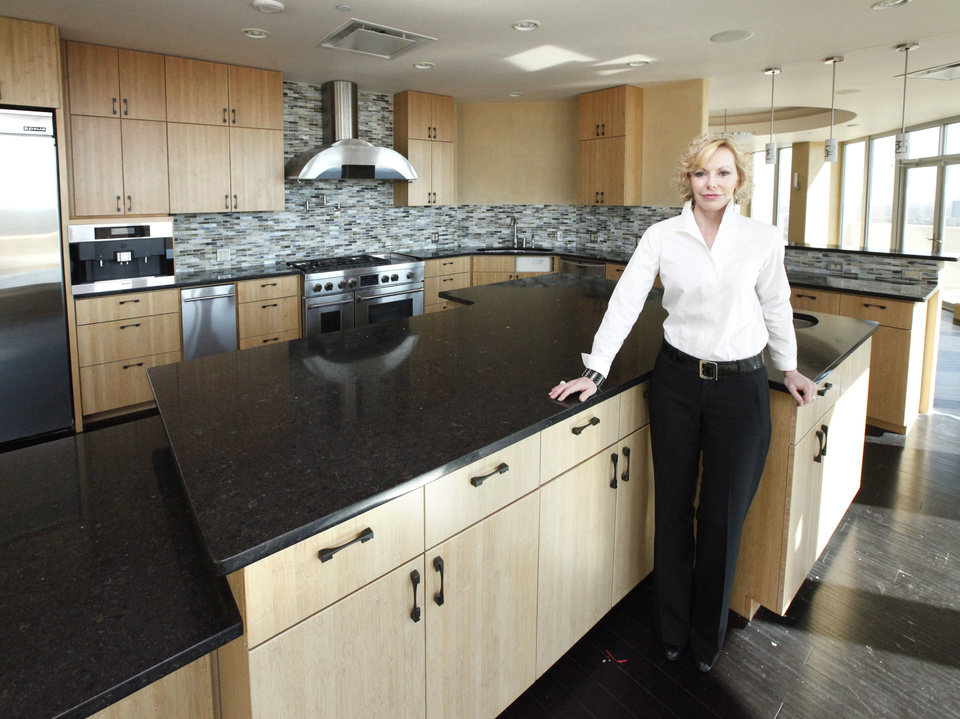 Photo - SkyBall c-chairwoman Sherry Crosthwait shows the kitchen of the 18th floor of Founders Tower Friday. Designers will deck out the nearly 7,000-square-foot penthouse for the 2014 Symphony Show House.  PAUL HELLSTERN - The Oklahoman