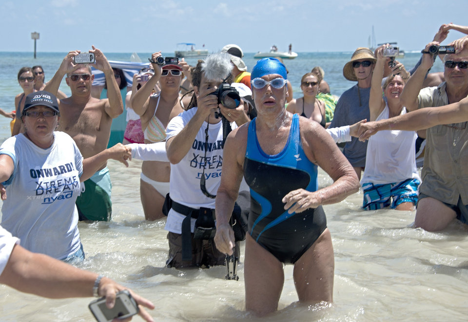 Photo - FILE - In this Monday, Sept. 2, 2013 file photo provided by the Florida Keys News Bureau, Diana Nyad emerges from the Atlantic Ocean after completing a 111-mile swim from Cuba to Key West, Fla. Nyad's swim from Cuba to Florida has generated some skepticism in the small community of marathon swimmers. Critics have suggested that during a speedy stretch of the 53-hour swim, Nyad might have gotten into or held onto the boat that accompanied her. They also question whether she violated the traditions of her sport by relying on a specialized mask and wetsuit to protect herself from jellyfish. Nyad's navigator and one of the swim's official observers tell The Associated Press that Nyad didn't cheat.  (AP Photo/Florida Keys Bureau, Andy Newman, File)