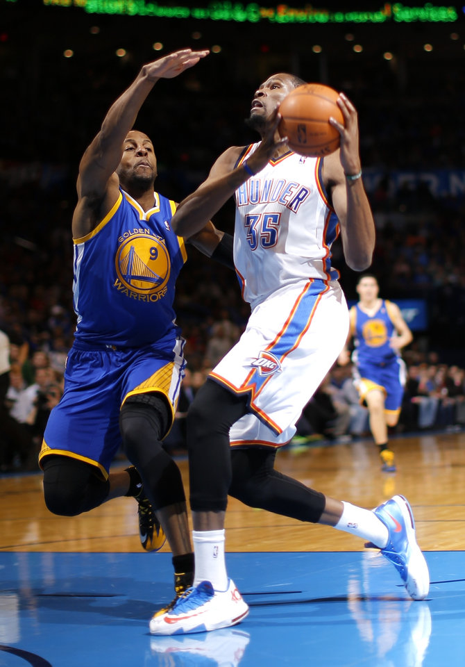 Photo - Oklahoma City's Kevin Durant goes past Golden State's Andre Iguodala during an NBA basketball game between the Oklahoma City Thunder and the Golden State Warriors at Chesapeake Energy Arena in Oklahoma City, Friday, Jan. 17, 2014. Photo by Bryan Terry, The Oklahoman