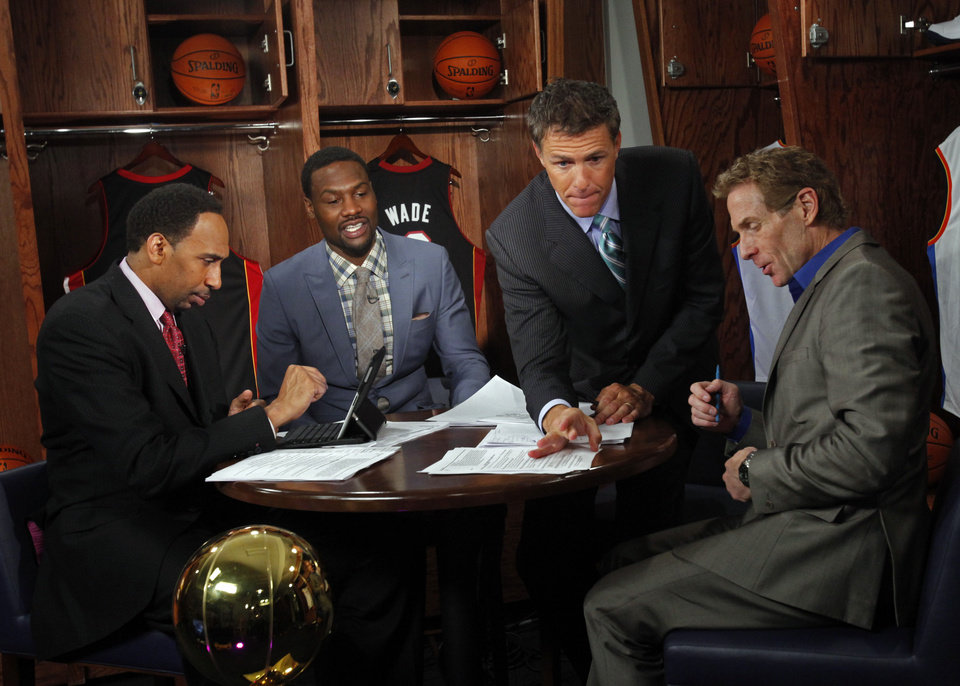 "ESPN ""First Take"" moderator Jay Crawford flicks a pesky fly off the table during a break in shooting the debate between Stephen A. Smith (left), and Skip Bayless (right) as guest Tony Allen sits in on the set inside a locker room before game two of the NBA basketball finals at the Chesapeake Energy Arena on Thursday, June 14, 2012 in Oklahoma City, Okla.  Photo by Steve Sisney, The Oklahoman <strong>STEVE SISNEY - THE OKLAHOMAN</strong>"