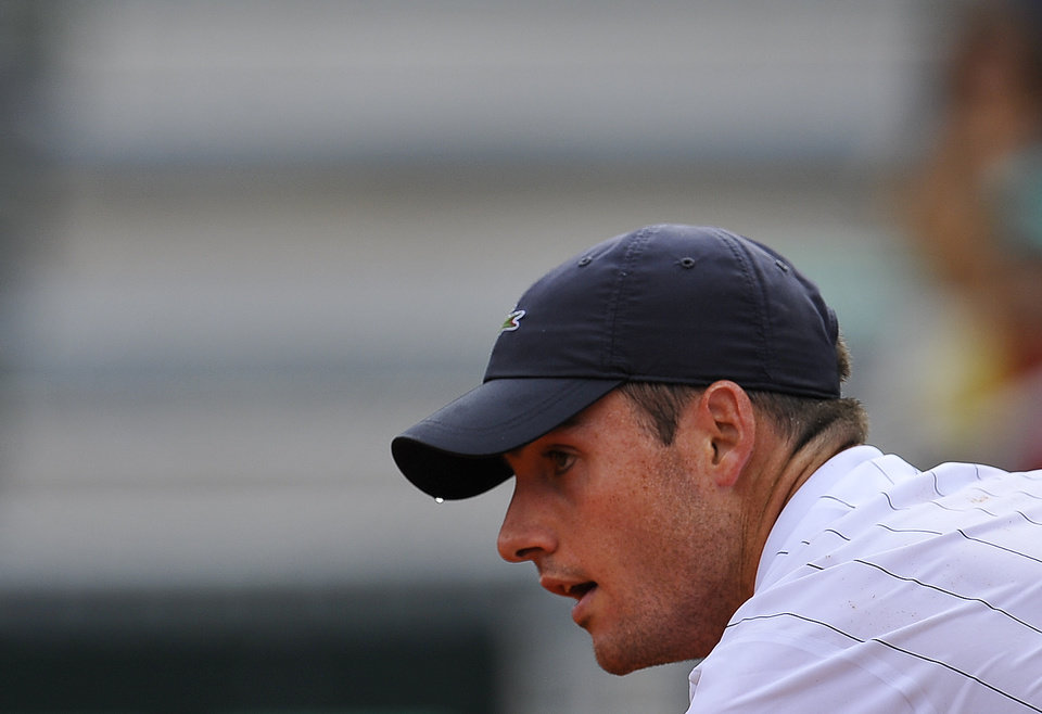 Photo -   John Isner of US, is concentrated on the match as a sweat drop clings to his peaked cap during his Davis Cup World Group Semi-final tennis match against Spain's David Ferrer, in Gijon, northern Spain, Sunday, Sept.16 , 2012. Ferrer won 6-7, 6-3, 6-4, 6-2. (AP Photo/Alvaro Barrientos)