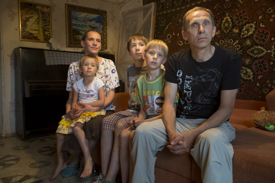 Photo - In this photo taken on Tuesday, May  27, 2014, Olga Mikhailova, left, and her husband Vladimir Mikhailov, right, pose for a photo with their children in their home in Slovyansk, Ukraine, Tuesday, May 27, 2014, after they decided to leave the city fearing the shelling attacks.  In Slovyansk, a city about 90 kilometers (55 miles) north of Donetsk which has been the scene of consistent clashes over the past few weeks, after residential areas on Wednesday came under mortar shelling from the government forces, with several people wounded and some buildings damaged in the attack.(AP Photo/Alexander Zemlianichenko)