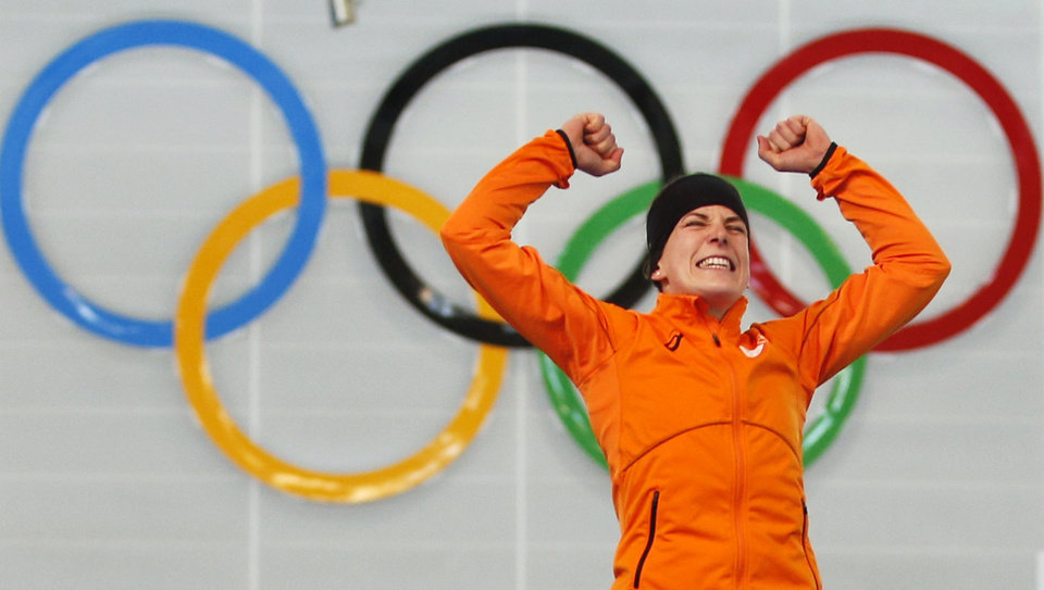 Photo - Ireen Wust of the Netherlands celebrates winning gold during the flower ceremony after winning gold in the women's 3,000-meter speedskating race at the Adler Arena Skating Center during the 2014 Winter Olympics, Sunday, Feb. 9, 2014, in Sochi, Russia.  (AP Photo/Pavel Golovkin)