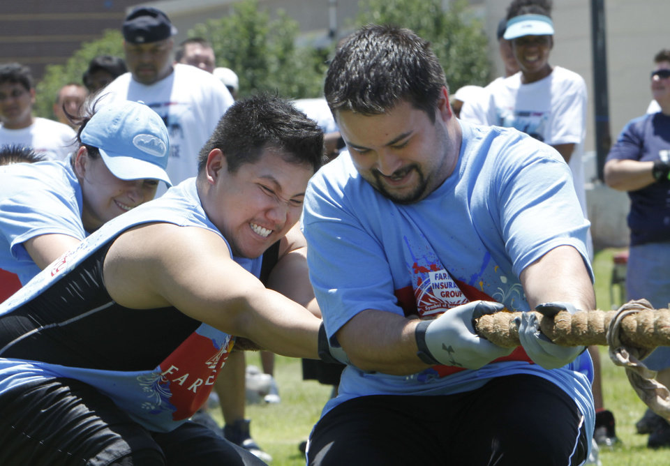 Photo - Richard Tran (left) and Patrick Nash compete in the tug-o-war event for Farmers Insurance during the OU Medicine Corporate Challenge at Bishop McGuiness High School in Oklahoma City, OK, Saturday, June 5, 2010. By Paul Hellstern, The Oklahoman ORG XMIT: KOD