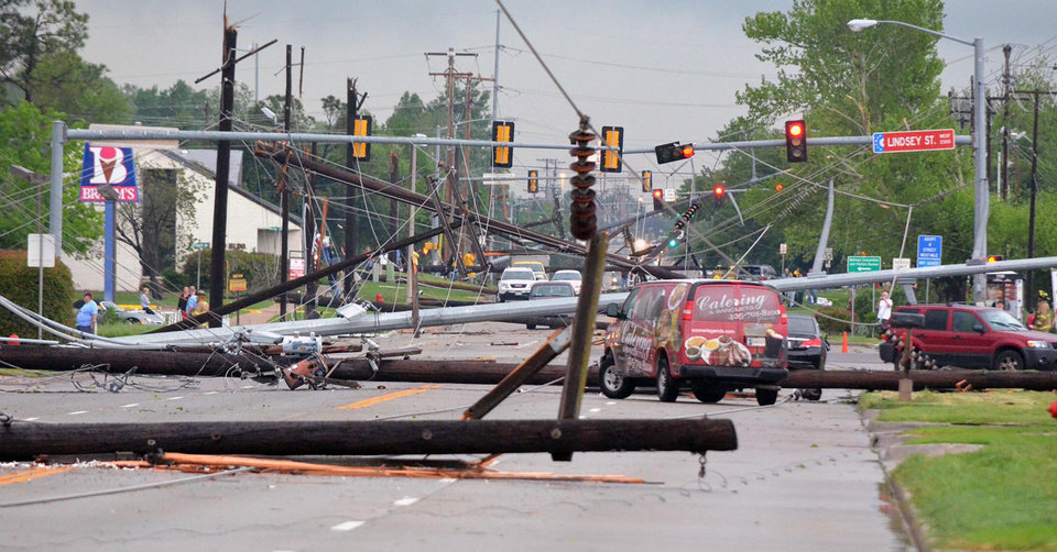 Photo -   Downed power lines litter 24th Avenue Southwest at the Lindsey Street intersection after a tornado hit Friday afternoon April 13, 2013 in Norman, Okla. (AP Photo/The Norman Transcript, Kyle Phillips)