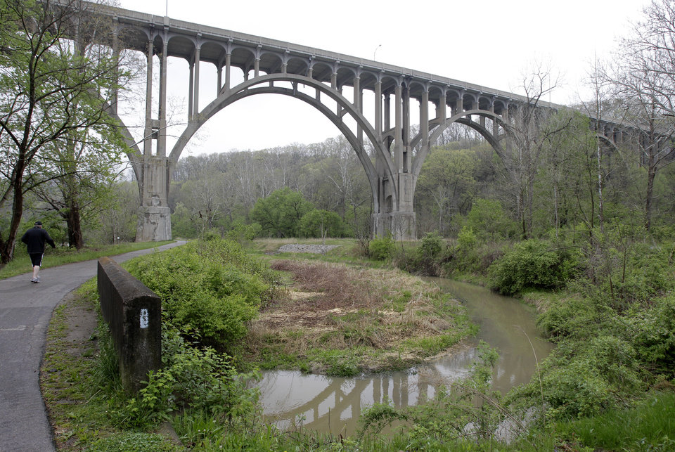 Photo -   A man walks along the tow path approaching the Station Rd. Bridge at the Cuyahoga Valley National Park in Brecksville, Ohio, Tuesday, May 1, 2012. Five men have been arrested for conspiring to blow up the high level bridge over the Cuyahoga River valley, but there was no danger to the public because the explosives were inoperable and were controlled by an undercover FBI employee, the agency said Tuesday in announcing the men's arrests. (AP Photo/Amy Sancetta)