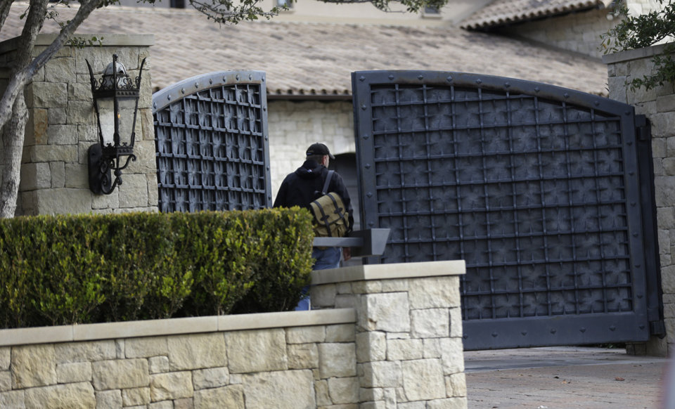 Photo - An unidentified man enters a gate at the home of cyclist Lance Armstrong, Monday, Jan. 14, 2013, in Austin, Texas. After more than a decade of denying that he doped to win the Tour de France seven times, Armstrong was set to sit down Monday for what has been trumpeted as a