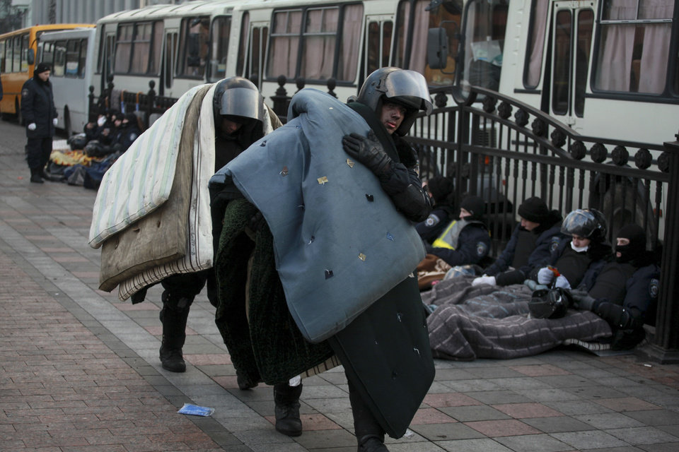 Photo - Police officers carry mattresses to take a rest at Ukraine's parliament in Kiev, Ukraine, Thursday, Feb. 20, 2014. Ferocious street battles between protesters and police in the Ukrainian capital have left dozens dead and hundreds wounded in the past few days, raising fears that the ex-Soviet nation, whose loyalties are split between Russia and the West, is in an uncontrollable spiral of violence.(AP Photo/Petro Zadorozhnyy)