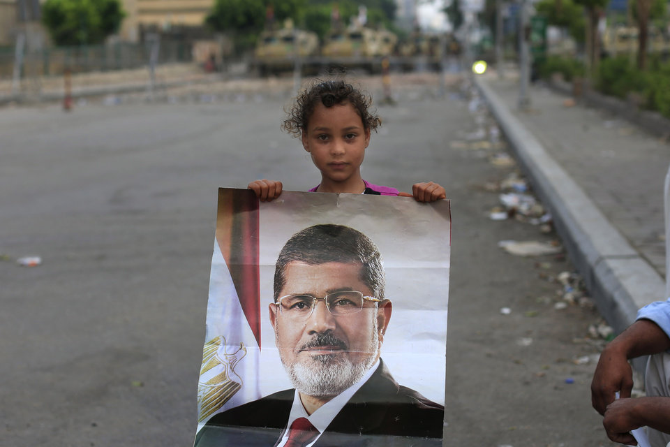 """Photo - A supporter of ousted Egypt's President Mohammed Morsi poses with his photo as army soldiers guard at the Republican Guard building in Nasr City, in Cairo, Egypt, Wednesday, July 10, 2013.  After days of deadlock, Egypt's military-backed interim president named a veteran economist as prime minister on Tuesday and appointed pro-democracy leader Mohamed ElBaradei as a vice president, while the army showed its strong hand in shepherding the process, warning political factions against """"maneuvering"""" that impedes the transition(AP Photo/Hassan Ammar)"""