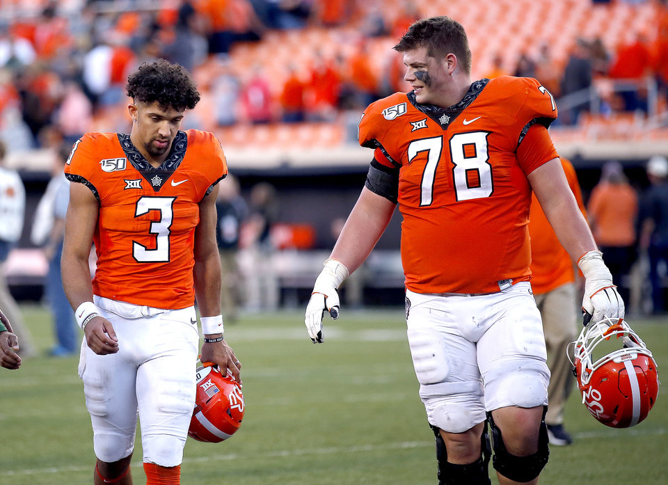 Photo - Oklahoma State's Spencer Sanders (3) and Bryce Bray (78) walk off the field following the college football game between Oklahoma State University and Baylor at Boone Pickens Stadium in Stillwater, Okla., Saturday, Oct. 19, 2019. Baylor won 45-27. [Sarah Phipps/The Oklahoman]