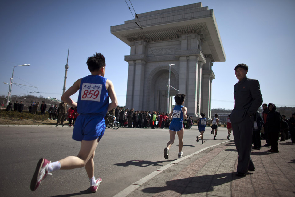 Photo - File - In this April 14, 2013 file photo, people watch runners near the Arch of Triumph in Pyongyang as North Korean hosts the 26th Mangyongdae Prize Marathon to mark the birthday of the late leader Kim Il Sung on April 15. For the first time ever, North Korea is opening up the streets of its capital to runner-tourists for the annual Pyongyang marathon, undoubtedly one of the most exotic feathers in any runner's cap. Tourism companies say they have been inundated by requests to sign up for the April 13, 2014 event, which this year will include amateur runners from around the world. (AP Photo/Alexander F. Yuan, File)