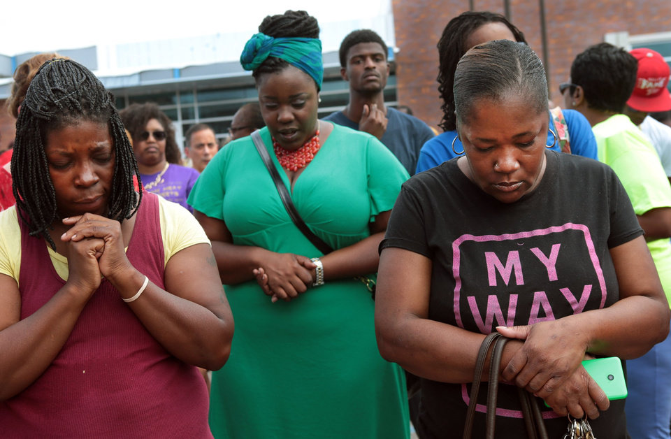 Photo - A prayer vigil was held in front of the Ferguson, Mo. police department on Sunday, Aug. 10, 2014, one day after a Ferguson officer shot and killed Michael Brown. From left are Martha Hightower, Leah Clyburn and Marie Wilson.