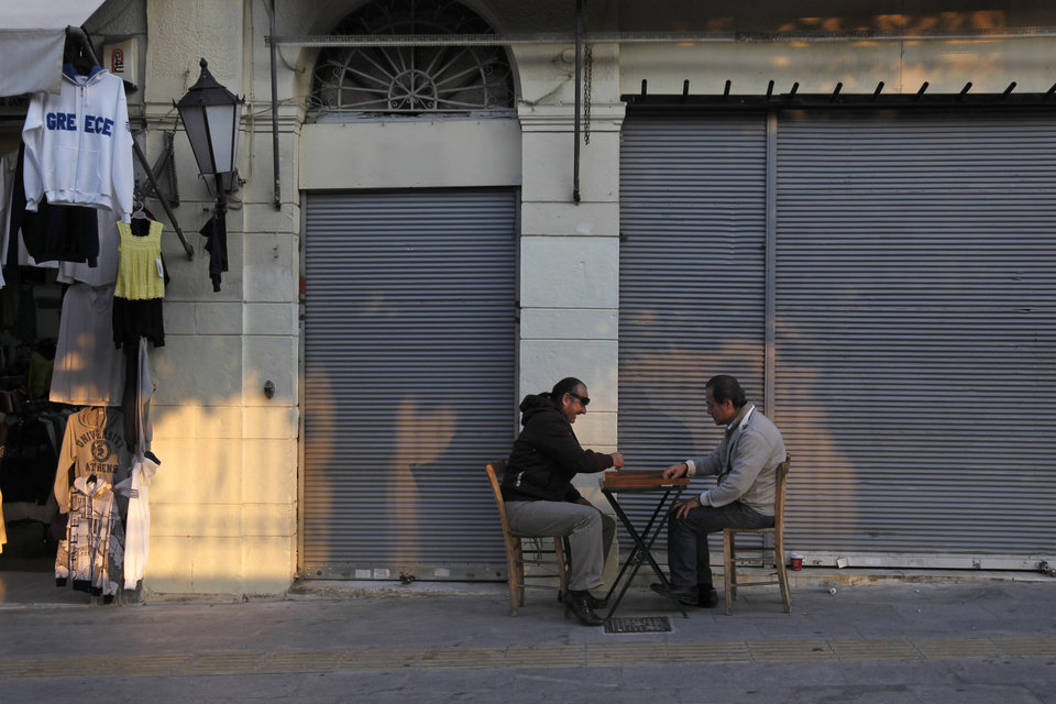 Shop owners play backgammon in the Plaka area of central Athens, on Tuesday, Nov. 1, 2011. Markets plunged Tuesday and Greece's beleaguered Socialist government faced collapse, a day after Prime Minister George Papandreou unexpectedly announced plans to hold a referendum on the latest international debt relief and bailout deal for his country. (AP Photo/Petros Giannakouris) ORG XMIT: ATH106