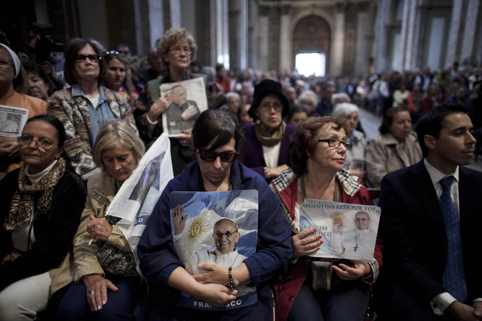 Photo - People holding images of Pope Francis attend Mass at the Metropolitan Cathedral in Buenos Aires, Argentina, Sunday, March 17, 2013.  Argentine's former Cardinal Jorge Mario Bergoglio was chosen as leader of the Catholic Church on March 13, 2013. (AP Photo/Natacha Pisarenko)