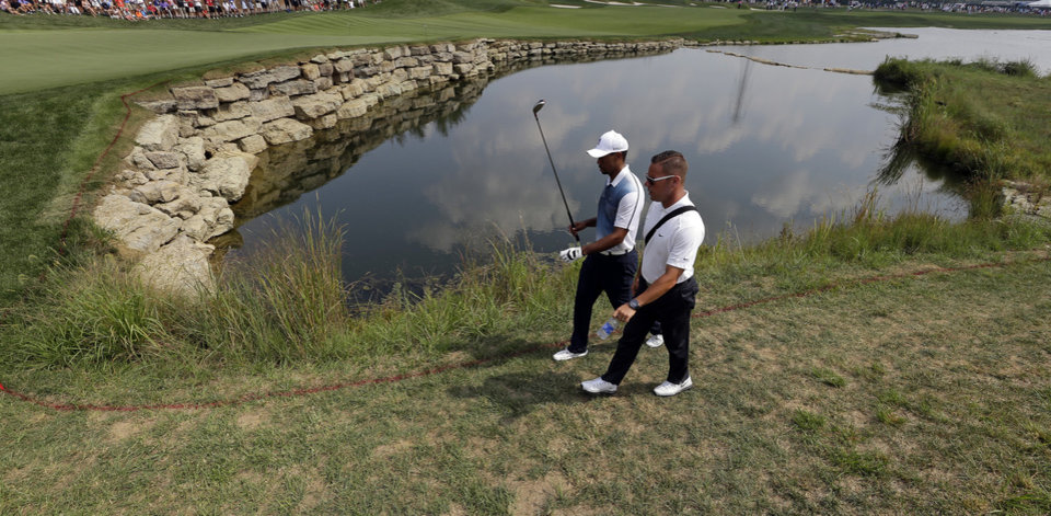 Photo - Tiger Woods, left, walks on the seventh hole with his swing coach Sean Foley during a practice round for the PGA Championship golf tournament at Valhalla Golf Club on Wednesday, Aug. 6, 2014, in Louisville, Ky. The tournament is set to begin on Thursday. (AP Photo/David J. Phillip)