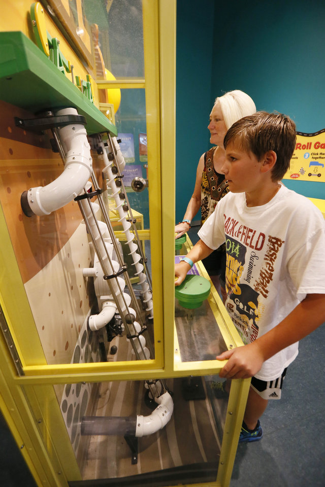 Photo - In this July 3, 2014 photograph, Jo Anne Ashley, right races her grandson John Gray, 10, of Lafayette, La., as they drill for oil on an interactive station at the  Mississippi Children's Museum in Jackson, Miss. The interactive hands-on facility promotes literacy, health and nutrition, learning the state's heritage and exploration of its cultural arts and key economic industries in a fun setting. (AP Photo/Rogelio V. Solis)