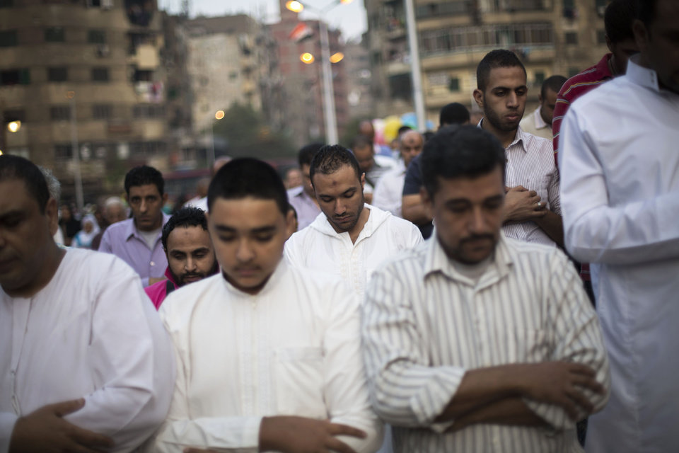 Photo - Egyptian men pray on a street next to the Sayyida Zeinab mosque on the first day of Eid al-Ahda in Cairo, Egypt, Tuesday, Oct. 15, 2013. Muslims worldwide are celebrating Eid al-Adha, or the Feast of the Sacrifice, by sacrificial killing of sheep, goats, cows or camels. The slaughter commemorates the biblical story of Abraham, who was on the verge of sacrificing his son to obey God's command, when God interceded by substituting a ram in the child's place. (AP Photo/Manu Brabo)