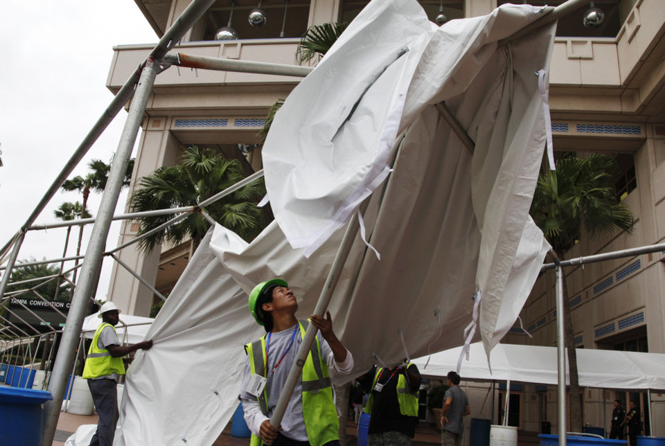 Photo - Joel Jimenez, right, and Issac Page remove an awning outside the Tampa Convention Center which serves as the media center for the Republican National Convention in Tampa, Fla., on Sunday, Aug. 26, 2012. Precautions were being taken in anticipation of Tropical Storm Isaac. (AP Photo/Lynne Sladky)  ORG XMIT: RNC501