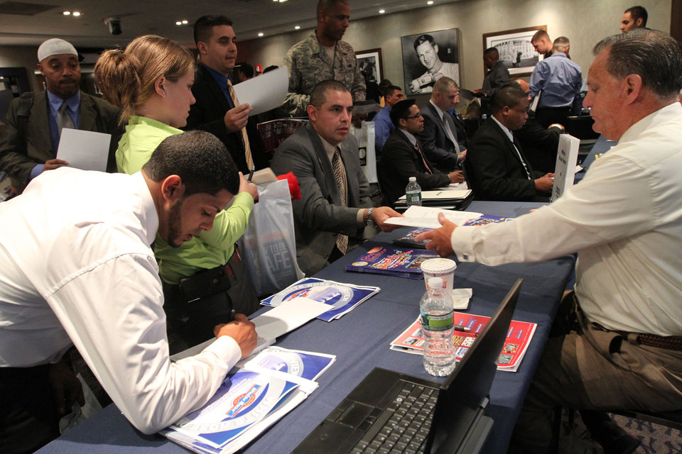 Photo -   In this Friday Sept. 28, 2012, photo, Veteran Luis Gomez, 40, from Dover, N.J., seated center, hands his resume to a representative from White Rose Foods, right, during a job fair at Yankee Stadium in the Bronx borough of New York. A private survey relased Wednesday, Oct. 3, 2012, shows that U.S. businesses hired fewer workers in September than August, a sign that slow growth may be holding back hiring. Payroll processor ADP said Wednesday that companies added 162,000 jobs last month. That's below August's total of 189,000, which was revised lower. (AP Photo/Tina Fineberg)