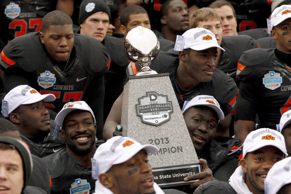 Photo - Oklahoma State Players pose for a photo with the Heart of Dallas Bowl trophy after the Heart of Dallas Bowl football game between Oklahoma State University and Purdue University at the Cotton Bowl in Dallas, Tuesday, Jan. 1, 2013. Oklahoma State won 58-14. Photo by Bryan Terry, The Oklahoman