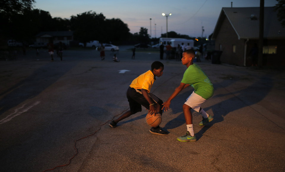 Photo - Michael Carter left, and Caleb White play basketball during midnight basketball at Christ Temple Community Church in Oklahoma City, Friday, July 25, 2014. Photo by Sarah Phipps, The Oklahoman