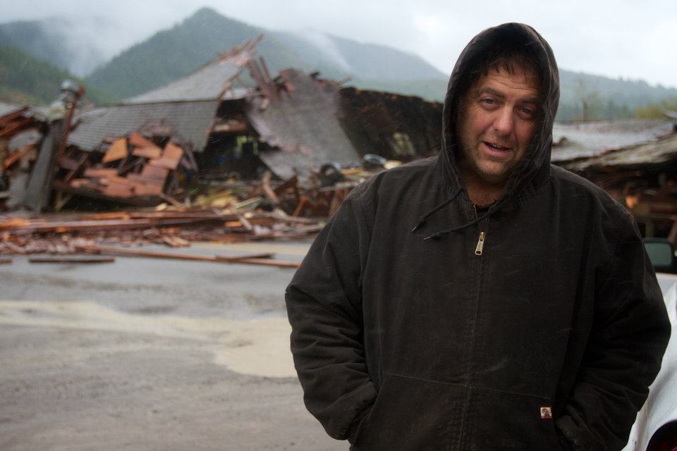Gary Petty's stands in front of his 1930-vintage barn which collapsed across the Kilchis River Road, east of Highway 101 near Tillamook, Ore., after high high winds hit the Oregon coast on Monday, Nov. 19, 2012. Residents in Washington and Oregon are bracing for expected river flooding after heavy rain and winds that caused sporadic road closures, power outages and at least one death. The wet weather is expected to continue throughout the week, after hurricane-strength winds battered both states along the coast. (AP Photo/The Oregonian, Randy L. Rasmussen)