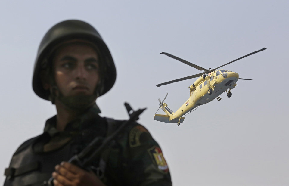Photo - A military solider stands guard as a helicopter carrying soon to be sworn in Abdel-Fattah el-Sissi lands near the Supreme Constitutional Court, in Cairo, Egypt, Sunday, June 8, 2014. Egypt's former army chief El-Sissi was sworn in on Sunday as president for a four-year term, taking the reins of power in a nation roiled since 2011 by deadly unrest and economic woes. (AP Photo/Amr Nabil)