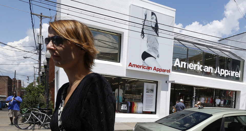 Photo -  Passers-by walk down the street past the American Apparel store in the Shadyside neighborhood of Pittsburgh on Wednesday. American Apparel Inc. said has reached a preliminary deal with investment firm Standard General to receive $25 million in financing to bolster the clothing chain's finances, a person close to the negotiations said Wednesday. AP PHOTO   Keith Srakocic